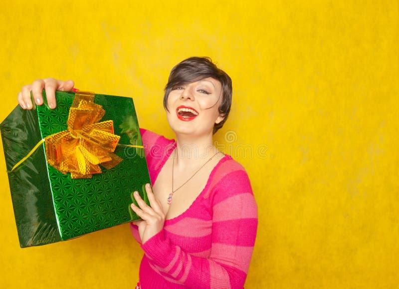 Fille mignonne dans le chandail rayé rose avec le grand cadeau vert avec l'arc sur le fond jaune de studio images stock