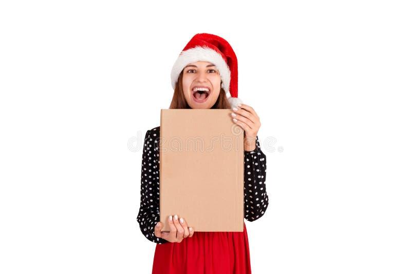 Fille mignonne dans le chapeau de chistmas étreignant ses cadeaux et regardant l'appareil-photo D'isolement sur le fond blanc Con photos libres de droits