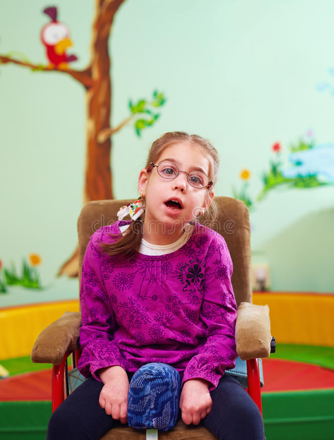 Fille mignonne dans le fauteuil roulant dans le jardin d'enfants pour des enfants avec les besoins spéciaux photographie stock libre de droits