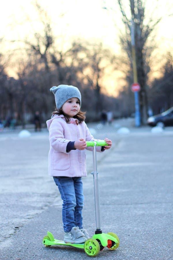 Fille mignonne dans un chapeau, un manteau et des jeans montant un scooter à trois roues Même le coucher du soleil de ville de re images stock