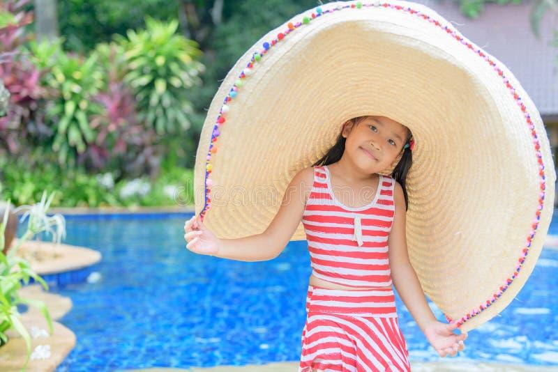 Fille mignonne dans un maillot de bain et un grand chapeau photo libre de droits