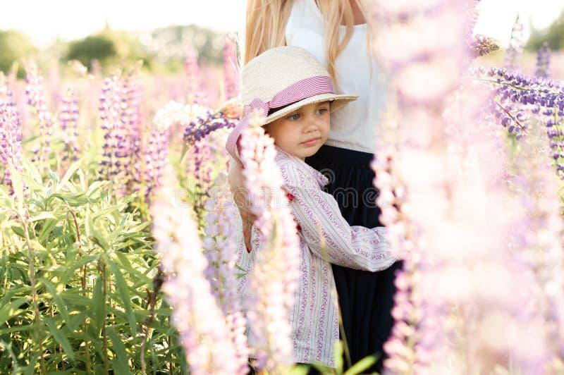 Fille mignonne dans une maman d'étreintes de chapeau dans un domaine des lupins photos libres de droits