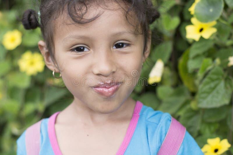 Fille mignonne de brune souriant avec le fond defocused de fleurs photographie stock libre de droits