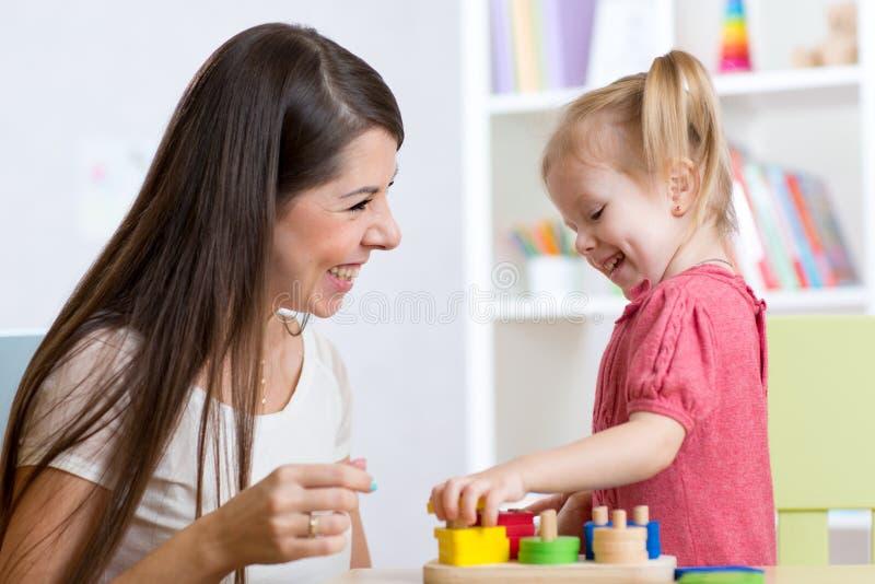 Fille mignonne de femme et d'enfant jouant les jouets éducatifs à la maison images libres de droits