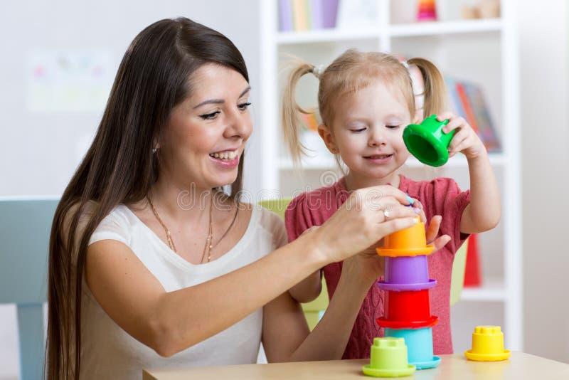 Fille mignonne de femme et d'enfant jouant les jouets éducatifs à la maison photo libre de droits