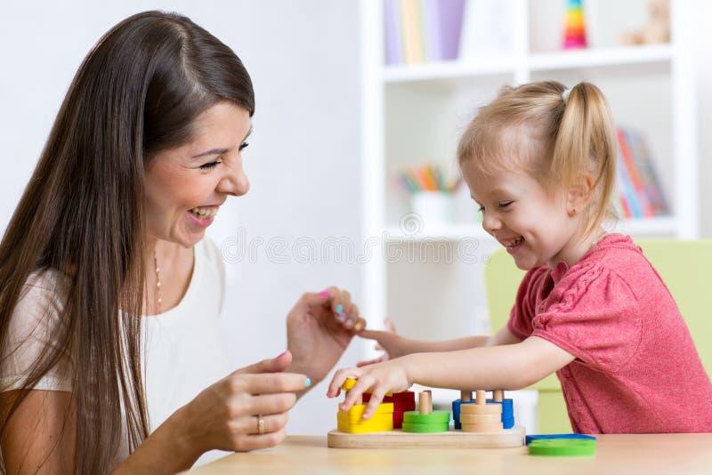 Fille mignonne de femme et d'enfant jouant les jouets éducatifs à la maison photo stock
