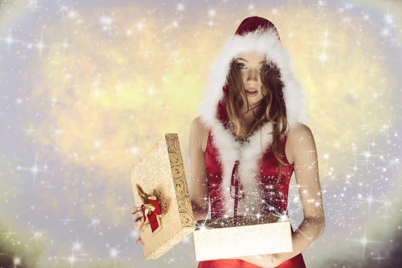 Fille mignonne de Noël ouvrant son cadeau photographie stock