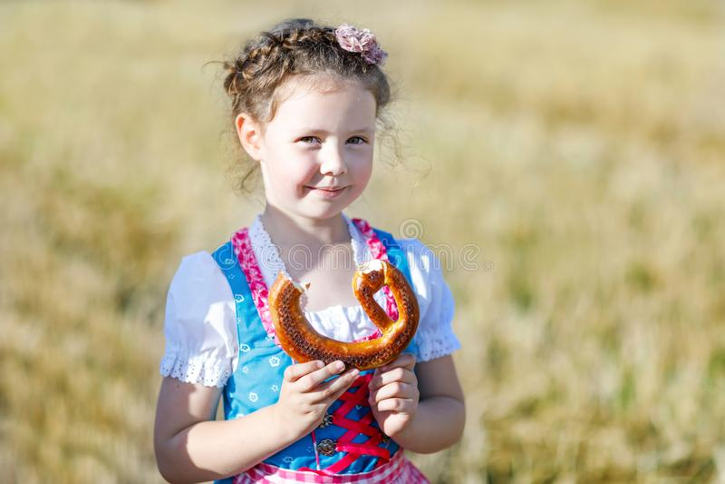 Fille mignonne de petit enfant dans le costume bavarois traditionnel dans le domaine de blé Enfant allemand avec la balle de foin photos stock