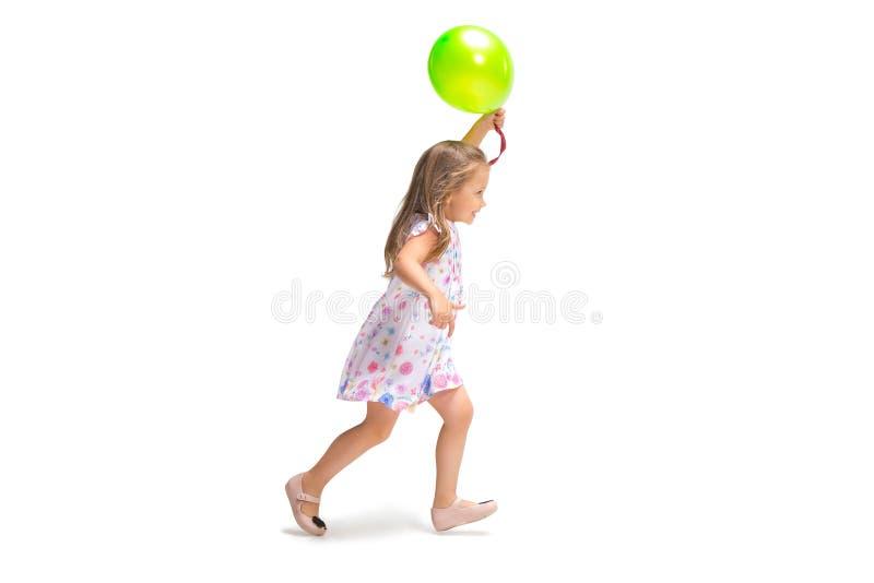 Fille mignonne de sourire d'enfant en bas âge trois ans fonctionnant au-dessus du fond blanc image stock