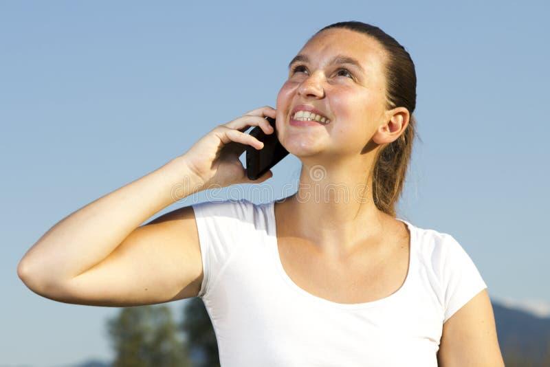 Fille mignonne de sourire parlant au téléphone image stock