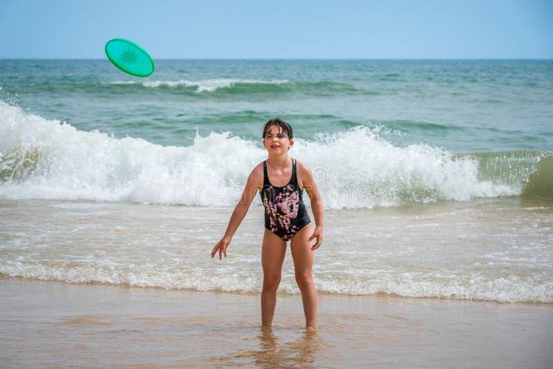Fille mignonne de youg dans le maillot de bain se tenant dans l'eau avec des vagues jetant un disque vert images stock