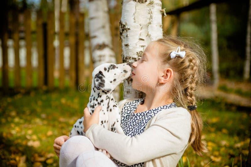 Fille mignonne embrassant son chiot, chienchien sur le fond en bois de barrière Fille heureuse avec un chien léchant son visage a images libres de droits
