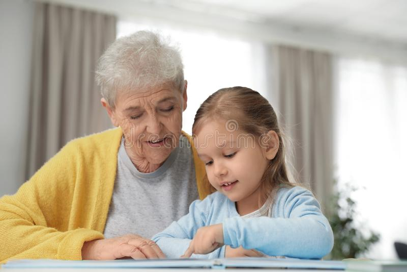 Fille mignonne et son livre de lecture de grand-mère photo stock