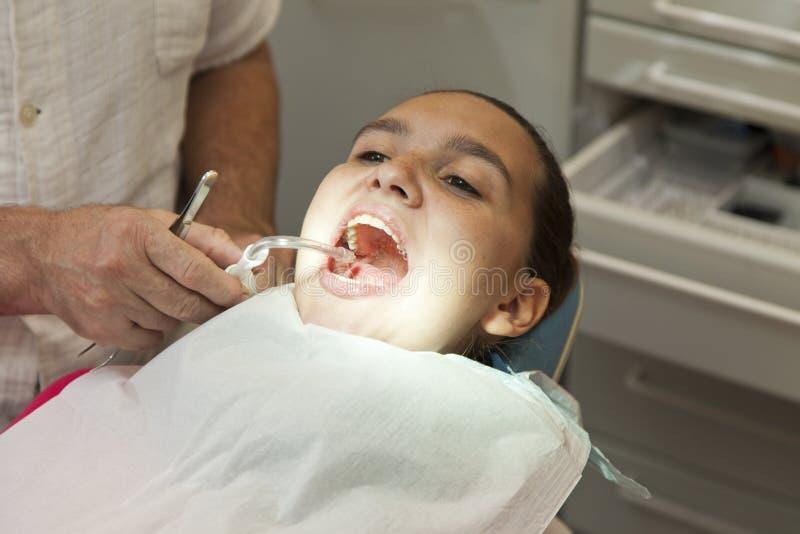 Fille mignonne faisant contrôler ses dents par le docteur image stock