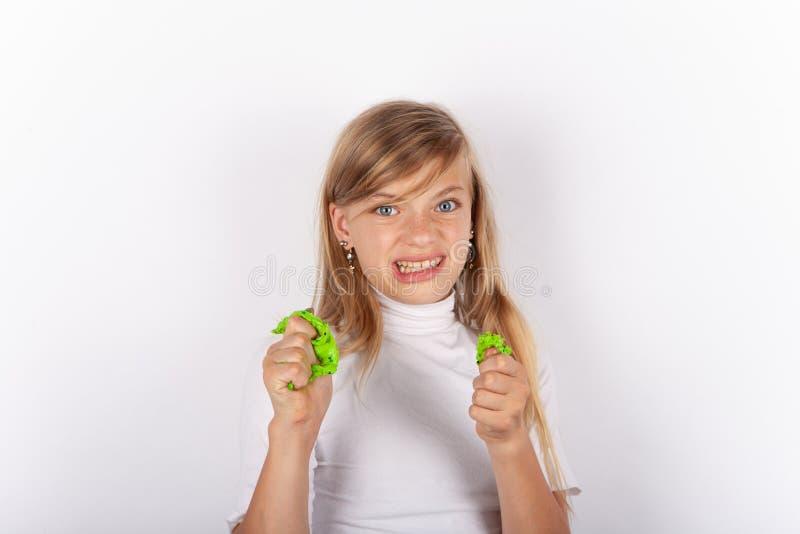 Fille mignonne faisant des visages tout en serrant des humeurs visqueuses dans des ses mains photos libres de droits