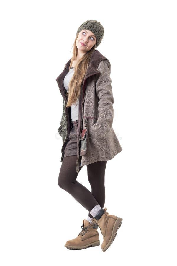 Fille mignonne fraîche géniale dans des vêtements élégants d'hiver recherchant pensants et ayants l'idée photo libre de droits