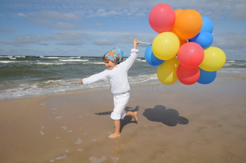Fille mignonne jouant avec des ballons sur la plage photos stock