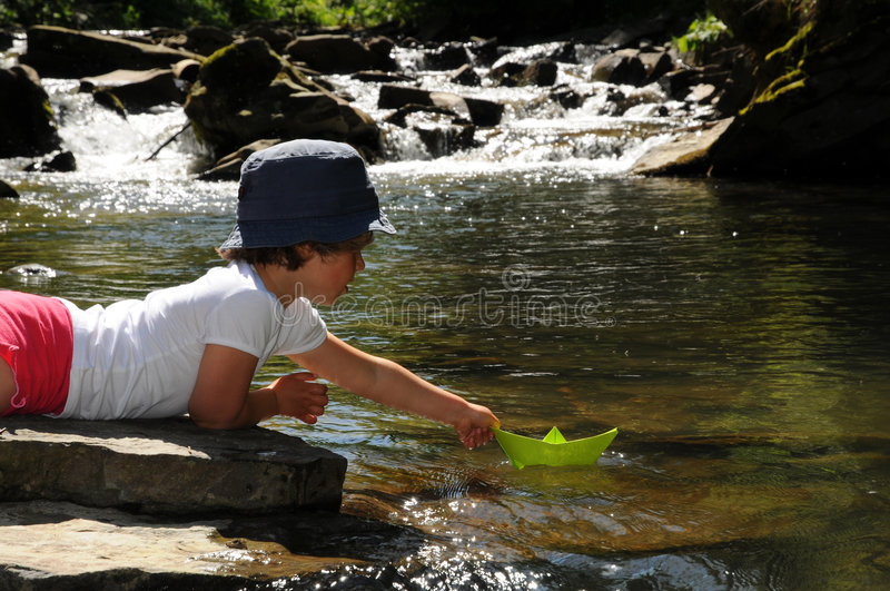 Fille mignonne jouant avec les bateaux de papier images stock