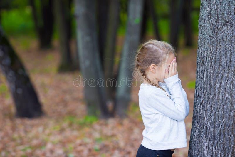 Fille mignonne jouant le cache-cache près de l'arbre dedans photos stock