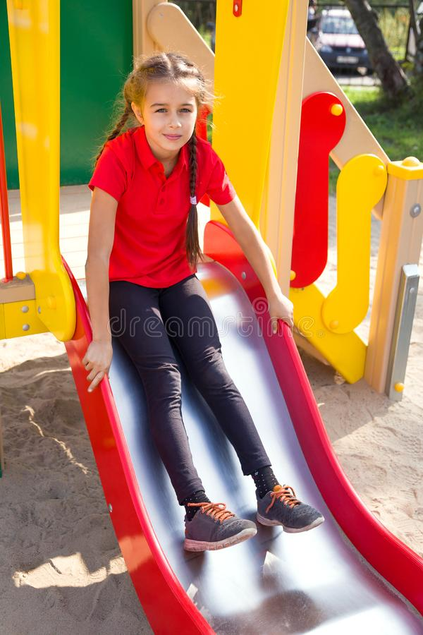 Fille mignonne jouant sur le terrain de jeu, ayant l'amusement sur une glissière photographie stock