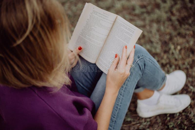 Fille mignonne lisant un livre tout en se reposant sur l'herbe en parc images stock