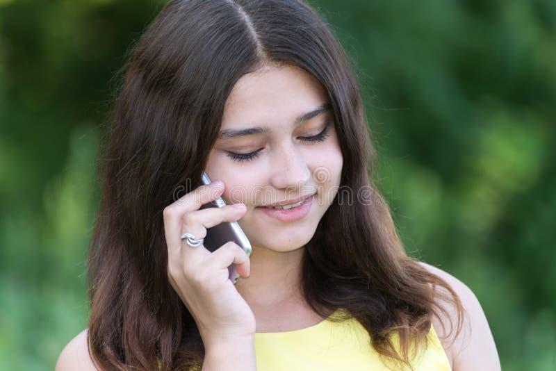 Fille mignonne parlant au téléphone en parc photographie stock