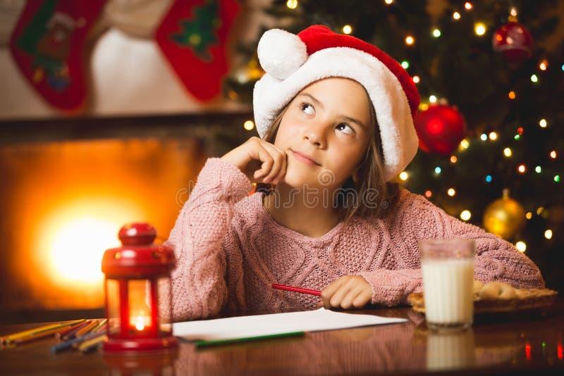 Fille mignonne pensant à la lettre à Santa au salon images stock