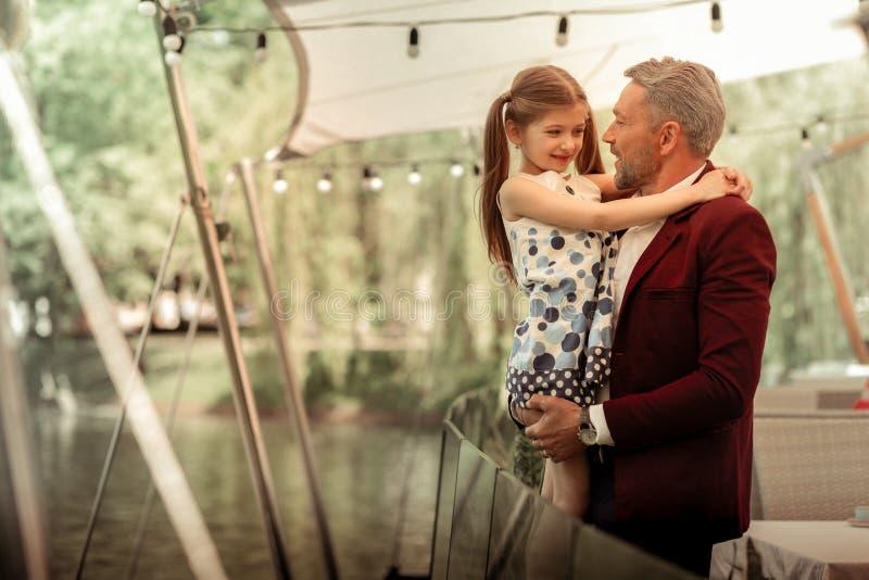 Fille mignonne portant la robe intéressante étreignant son père affectueux photographie stock
