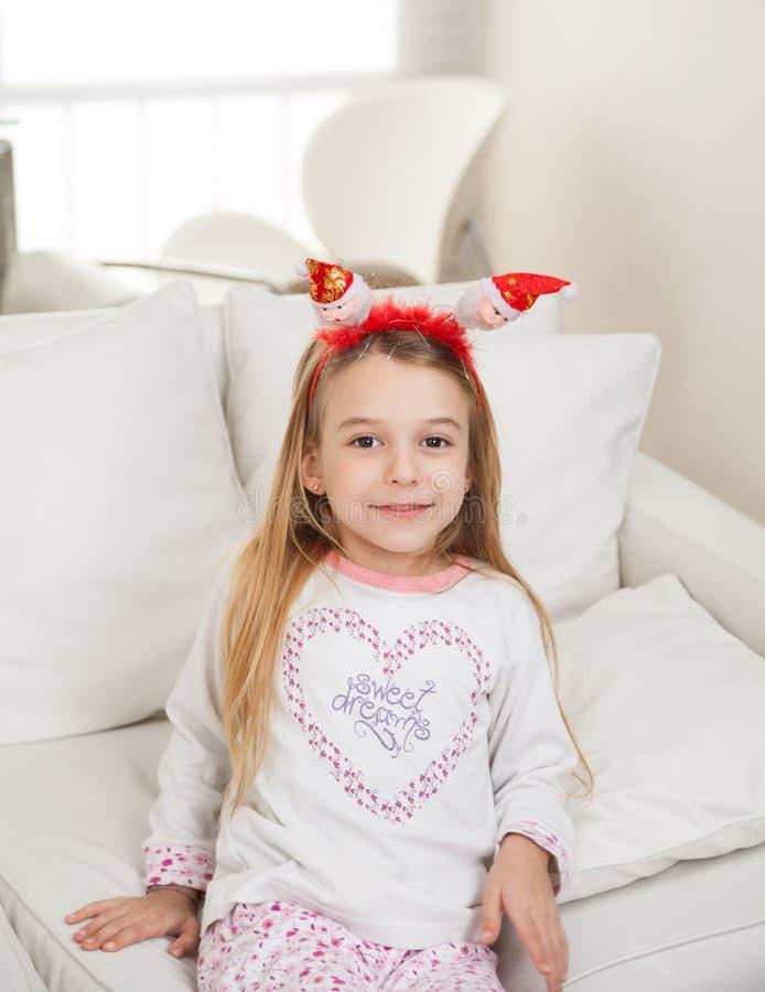 Fille mignonne portant Santa Headband At Home images stock