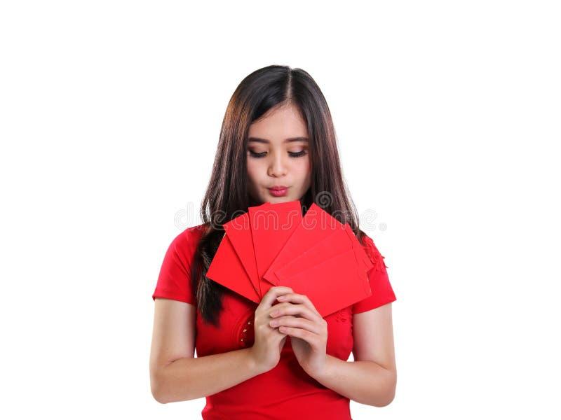 Fille mignonne regardant les enveloppes rouges sur ses mains, portrait de plan rapproché sur le fond blanc photo stock