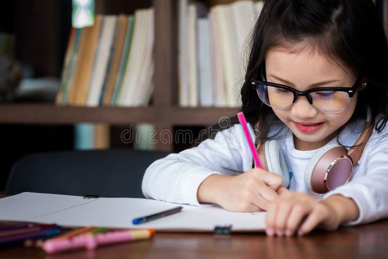 Fille mignonne sourie et sur le tas à dessiner un livre dans la bibliothèque, c image stock