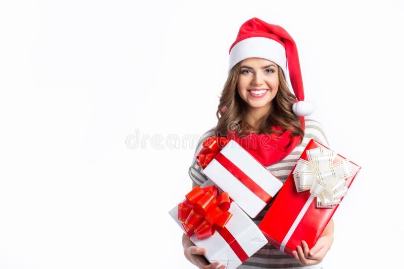 Fille mignonne tenant des cadeaux de Noël et de nouvelle année Fille de Noël dans le chapeau de Santa avec des boîtes photos libres de droits