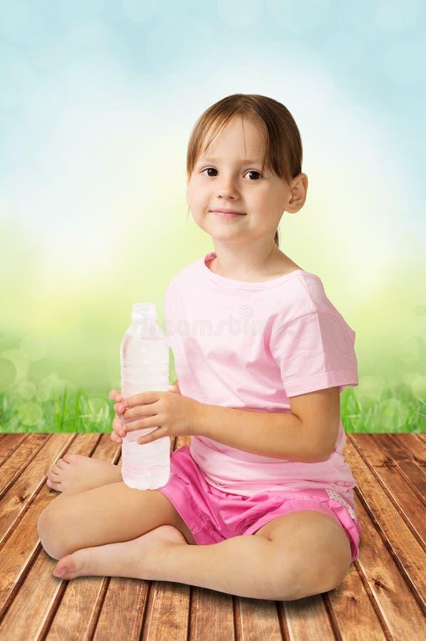 Fille mignonne tenant la bouteille de l'eau photos stock