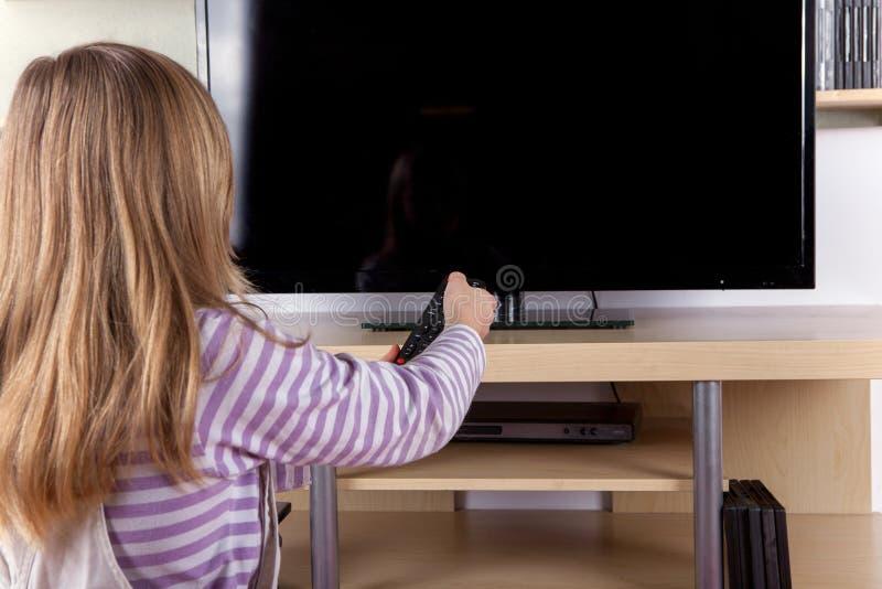 Fille mignonne tournant 'Marche/Arrêt' la télévision avec un à télécommande photo libre de droits