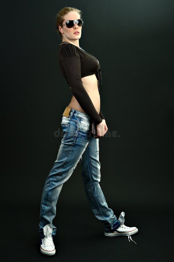 Fille mince dans des jeans avec des lunettes de soleil sur cyan images stock