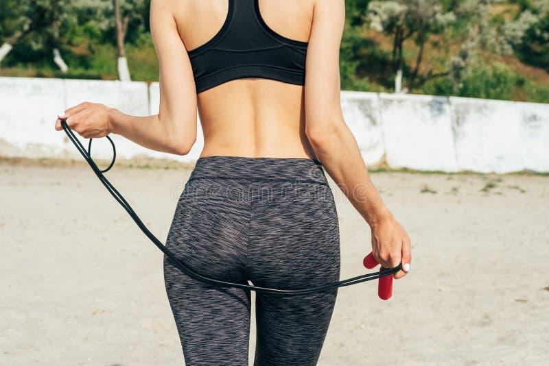 Fille mince dans les vêtements de sport sur la plage tenant une corde à sauter rouge images stock