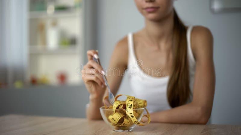 Fille mince mangeant la bande de mesure, concept de calorie comptant, indice de masse corporelle photos stock