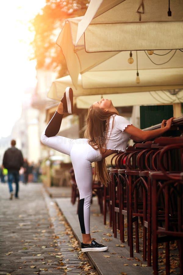 Fille mince sportive de sport faisant étirant des exercices sur la rue de ville à la lumière de coucher du soleil image stock
