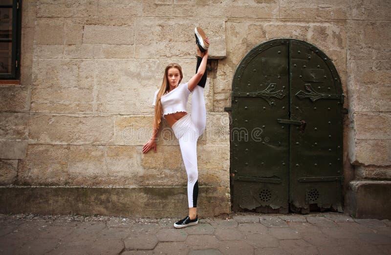 Fille mince sportive de sport faisant étirant des exercices sur la rue de ville sur le fond du mur en pierre de cru photos libres de droits