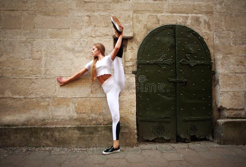 Fille mince sportive de sport faisant étirant des exercices sur la rue de ville sur le fond du mur en pierre de cru images libres de droits