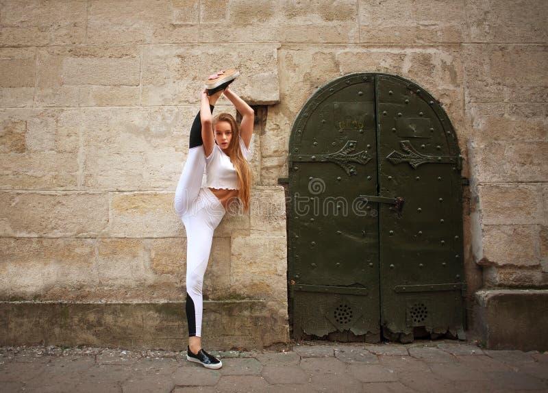 Fille mince sportive de sport faisant étirant des exercices sur la rue de ville sur le fond du mur en pierre de cru photographie stock