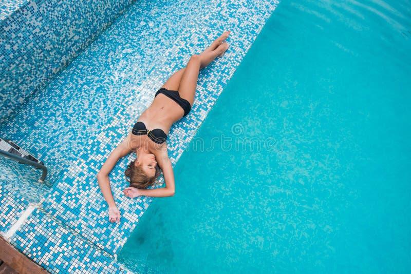 Fille mince withBeautiful de belle fille mince avec les cheveux blonds dans un maillot de bain se situant dans la piscine, vue su photographie stock libre de droits