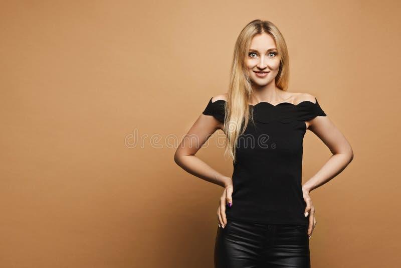 Fille modèle blonde belle et de yound avec le corps parfait mince dans le pantalon en cuir noir et dans un chemisier noir posant  images libres de droits