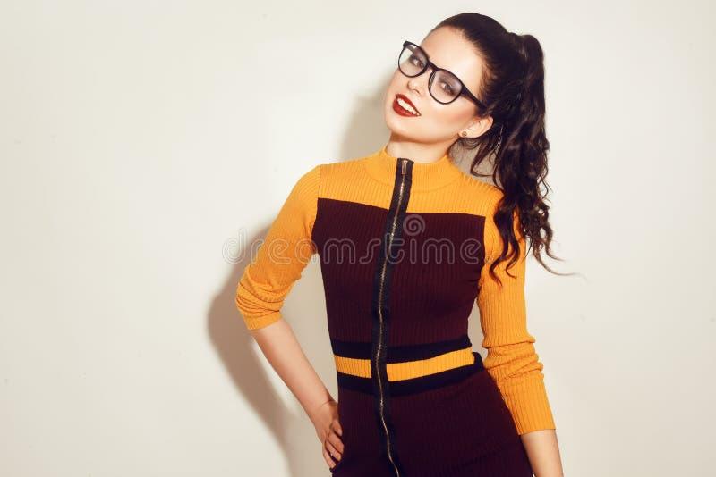 Fille modèle de brune de mode de beauté portant les lunettes élégantes Femme sexy avec le maquillage parfait, la robe orange et r photos libres de droits