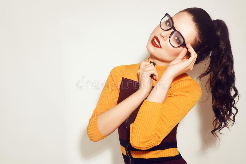 Fille modèle de brune de mode de beauté portant les lunettes élégantes Femme sexy avec le maquillage parfait, la robe orange et r images libres de droits