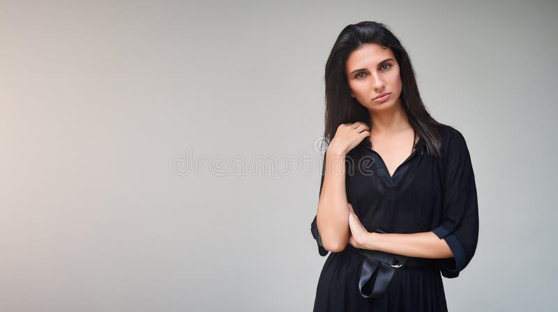 Fille modèle de brune portant la robe noire élégante Portrait sexy de femme avec le maquillage parfait, tendances de beauté Photo image libre de droits