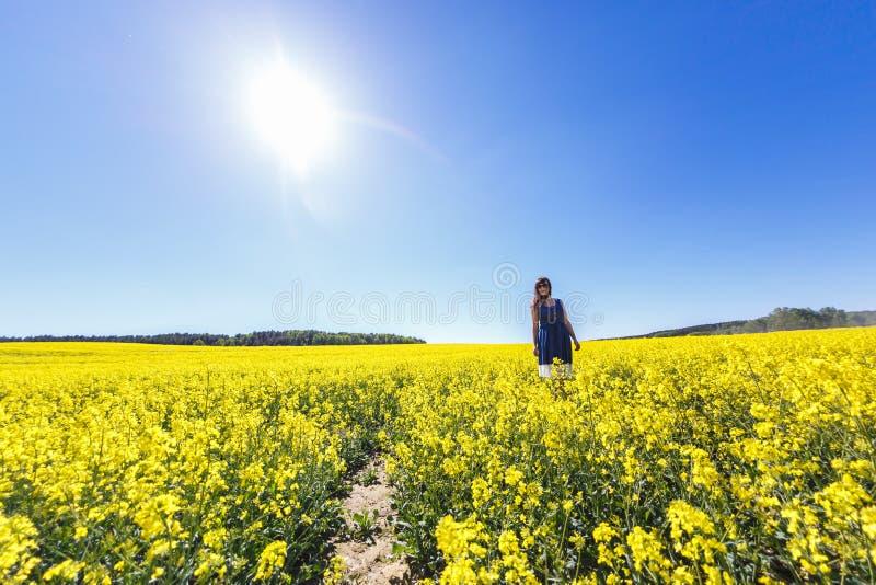Fille modèle de jeune belle grande taille heureuse dans la robe bleue sur le gisement de floraison de graine de colza en été Suiv image libre de droits
