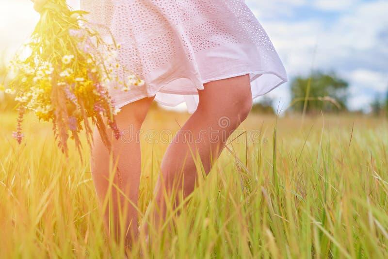 Fille modèle heureuse dans la robe blanche marchant sur le champ sur le coucher du soleil ou le lever de soleil avec des wildflow images libres de droits