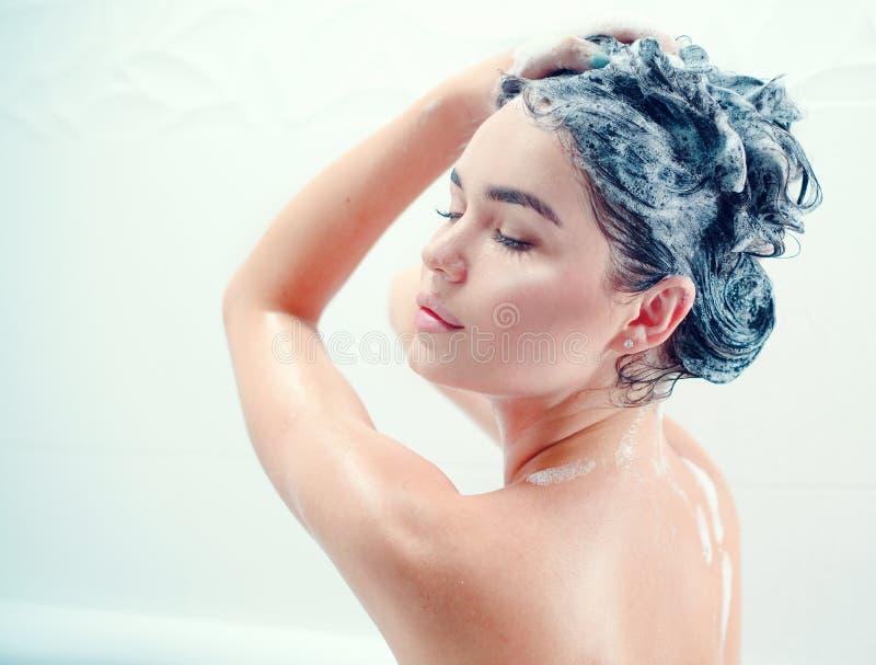 Fille modèle sexy de beauté se lavant les longs cheveux noirs avec un shampooing photos stock