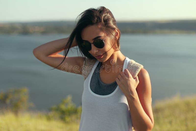 Fille moderne dans des lunettes de soleil se tenant au soleil photographie stock